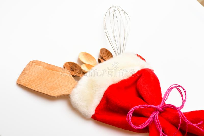 Kitchen accessories or tools. Christmas gift concept. Kitchen accessories or kit of kitchenware packed in big red sock royalty free stock photo