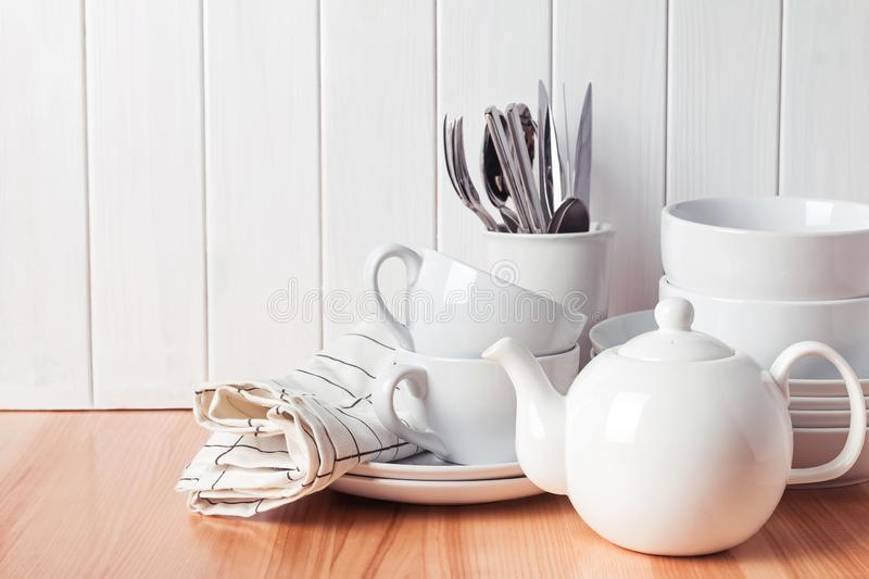 Different tableware, plates, cups standing near the white wooden wall stock photography