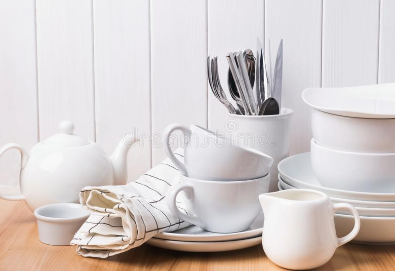 Different tableware, plates, cups standing near the white wooden wall royalty free stock images
