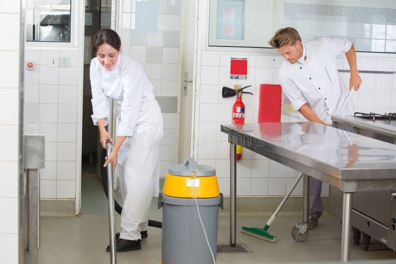 Kitchen aids cleaning restaurant kitchen. Kitchen aids are cleaning the restaurant kitchen stock photography