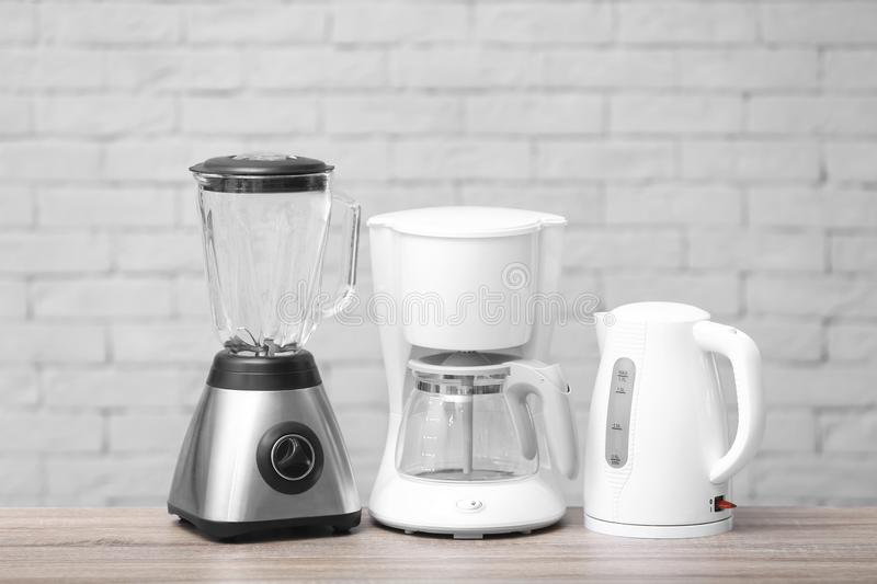 Kitchen appliances on table against brick wall background. Interior element royalty free stock photos