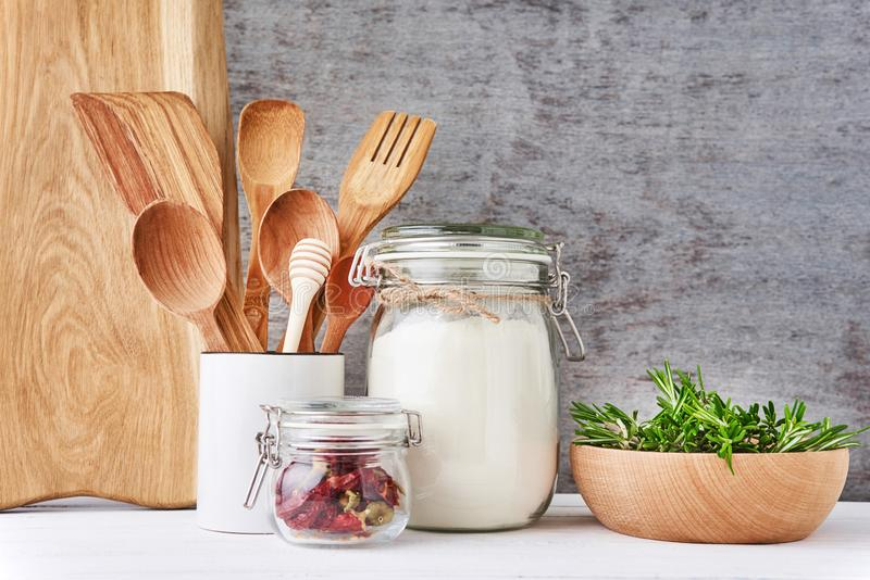 Kitchen background with cutting board, wooden cutlery and rosemary on a white table royalty free stock image