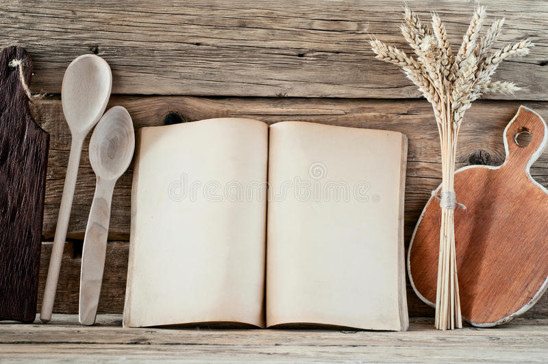 Kitchen book with blank pages. To write text on the wooden background with wooden spoons, cutting board and wheat spikelets. Copy space. Food background stock images