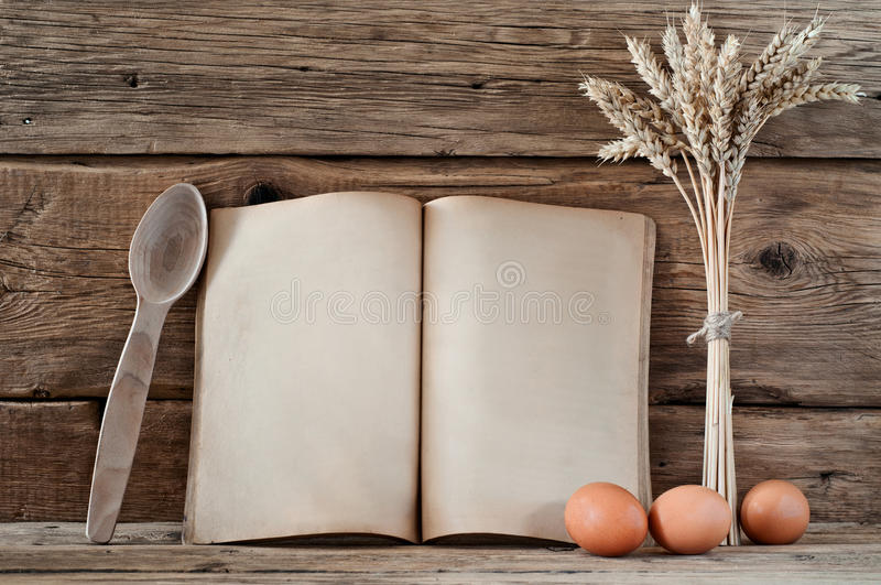 Kitchen book with blank pages. To write text on the wooden background with wooden spoons, raw eggs and wheat spikelets. Copy space. Food background stock images