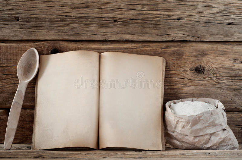 Kitchen book with blank pages. To write text on the wooden background with wooden spoons and small sack of flour. Copy space. Food background royalty free stock image