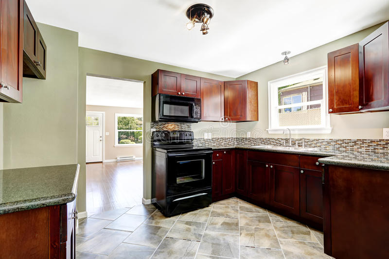 Kitchen With Bright Burgundy Cabinets And Black Appliances ...