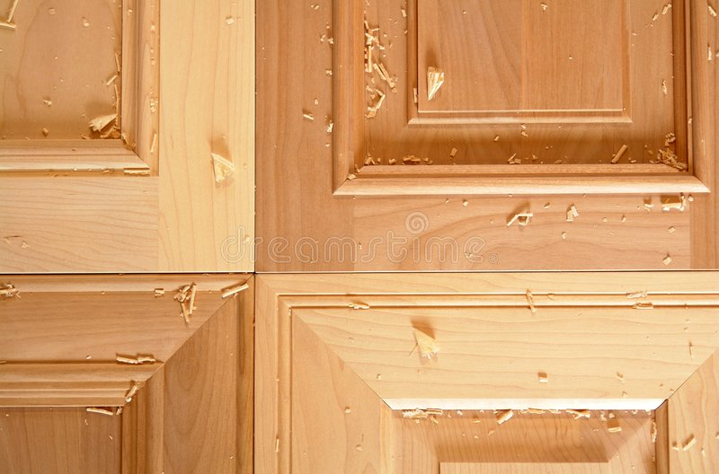 Kitchen Cabinet Doors. Four different hardwood door styles covered in maple shavings royalty free stock photography