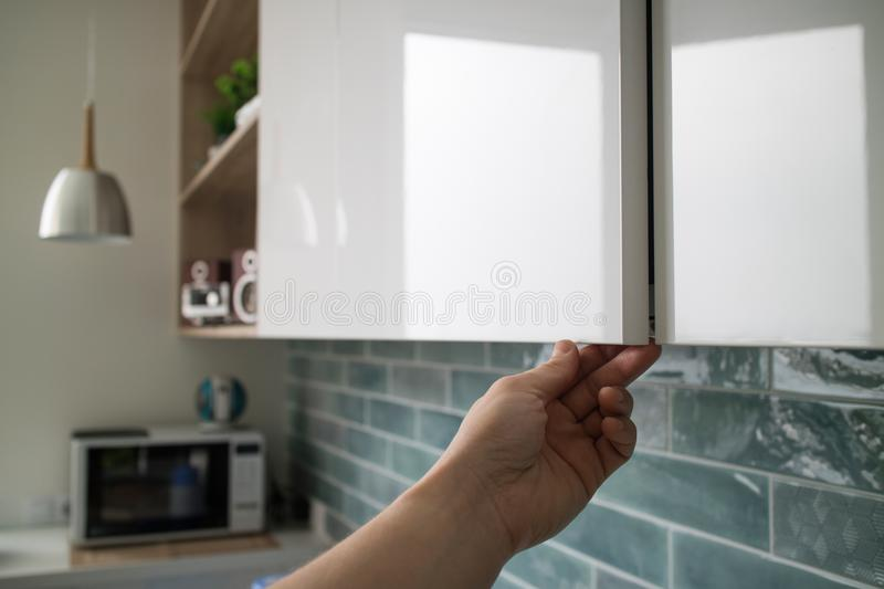 Kitchen cabinet with doors without handles, the man`s hand shows how the doors open without handles. A modern kitchen design with a cabinet without handles, the royalty free stock photos