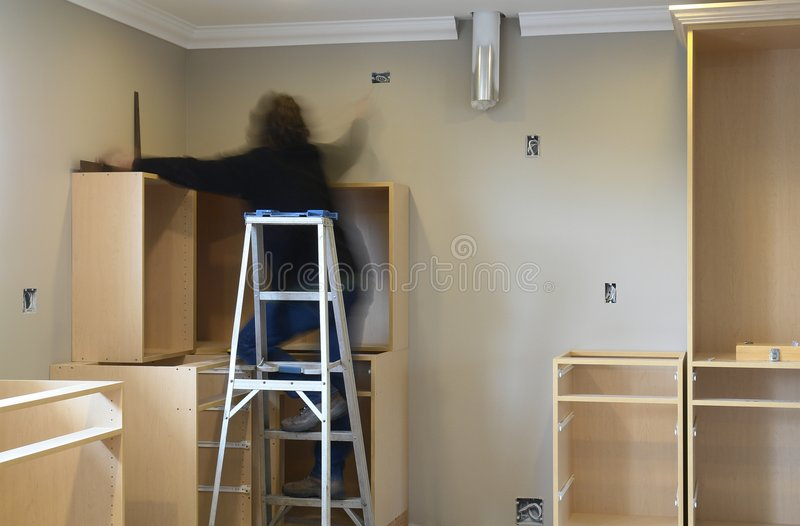 Kitchen Cabinet Install Home. Cabinetmaker working at installing new kitchen cabinets in a home renovation royalty free stock images