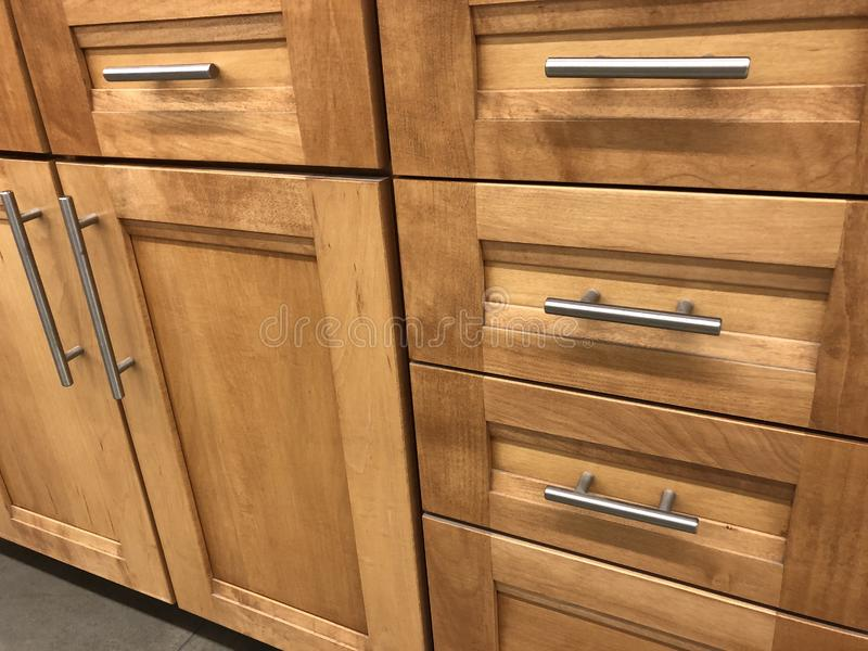 Kitchen cabinets made of natural wood maple with chrome handles royalty free stock image