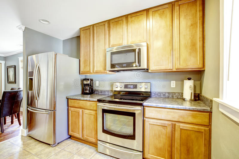 Kitchen cabinets and steel appliances. Light tones kitchen cabinets with grantie top and steel appliances royalty free stock photos
