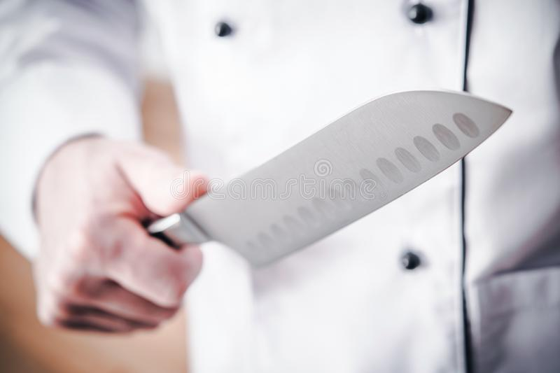 Kitchen Chef with Knife. Kitchen Chef with Large Sharp Knife in a Hand. Meal Preparation stock photo