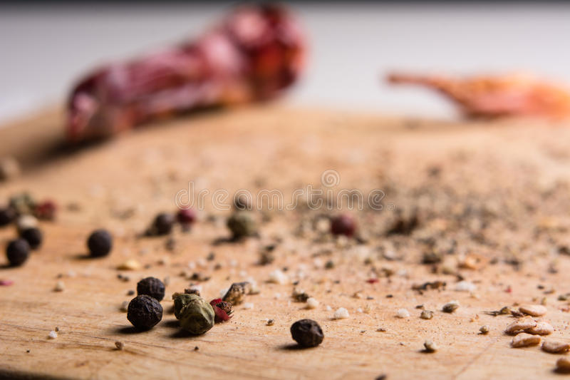 In kitchen chopping board ground pepper and peas. In the kitchen chopping board ground pepper and peas. Close-up of a wooden background with chilli menu royalty free stock images