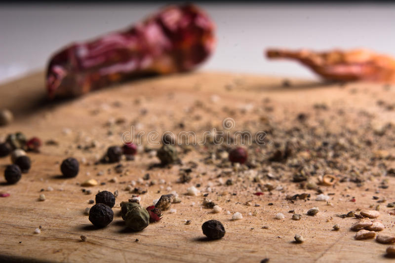 In kitchen chopping board ground pepper and peas. In the kitchen chopping board ground pepper and peas. Close-up of a wooden background with chilli menu royalty free stock photography