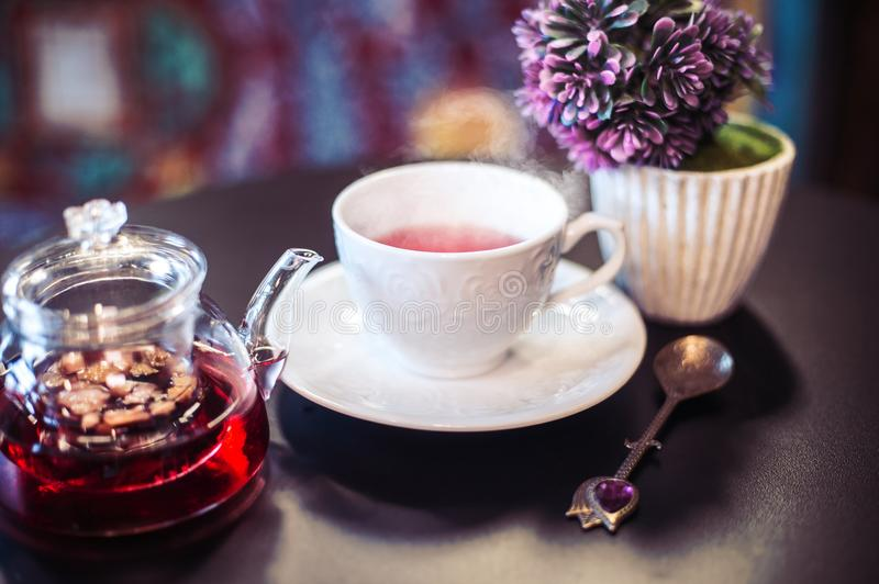Still life herbal fruit tea with. Kitchen composition of a teapot with t tea, elegant white cup with steam coming from it and purple oriental background royalty free stock photography