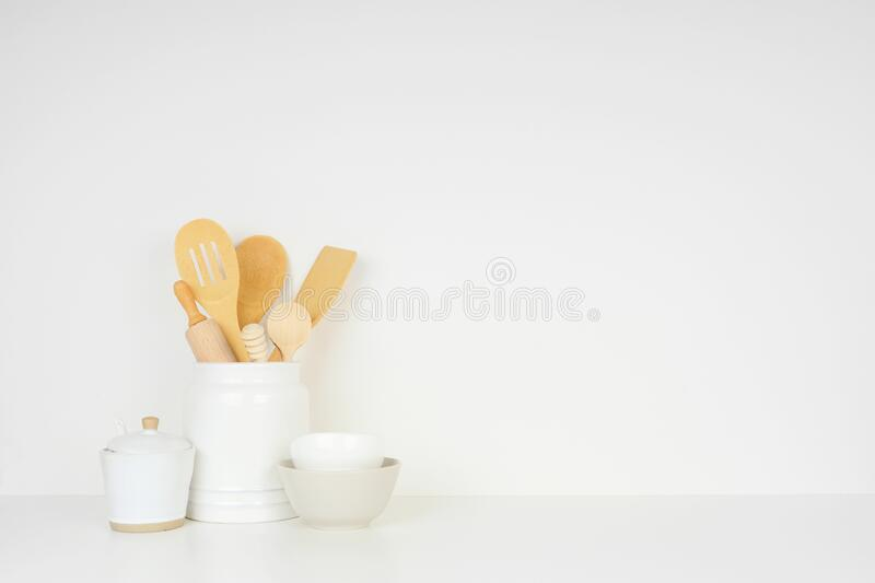 Kitchen cooking utensils on a white shelf or counter against a white wall background royalty free stock image