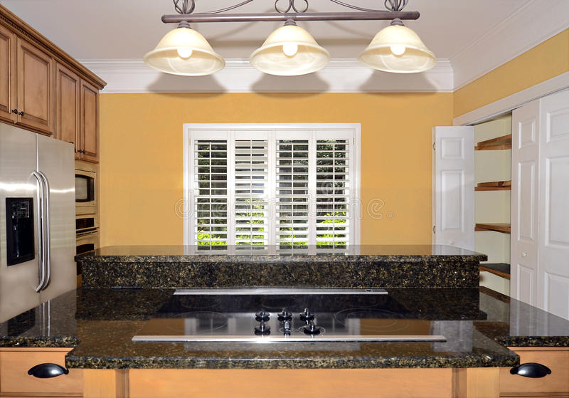 Kitchen Cooktop Area. The cooktop and counter in a kitchen showing a pantry, refrigerator, cabinets, and window with shutters. The walls have a slight texture stock photos
