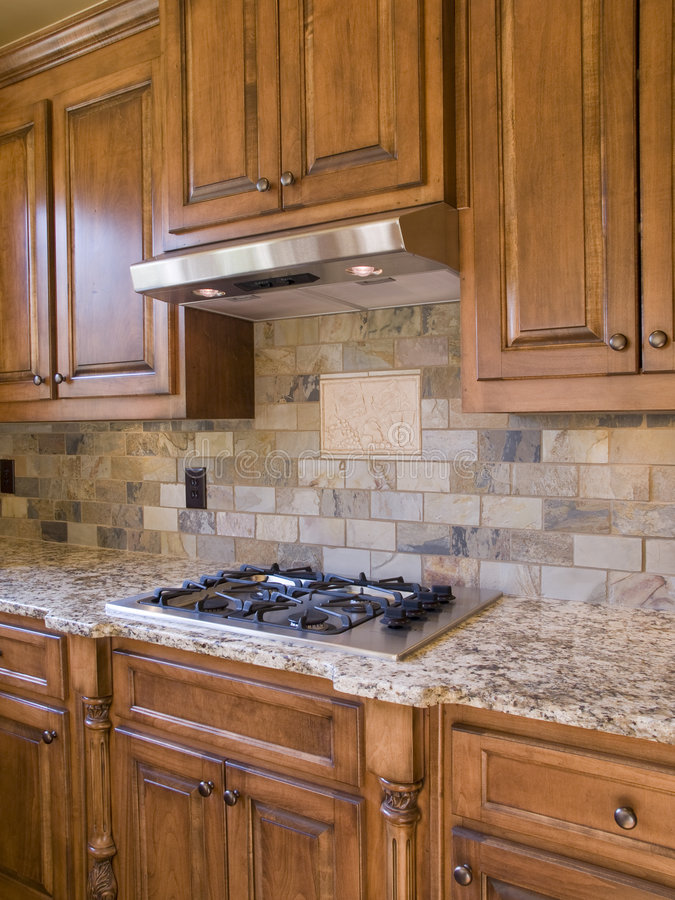 Kitchen cooktop and cabinets angle view. Kitchen cooktop and wood cabinets angle view royalty free stock photos