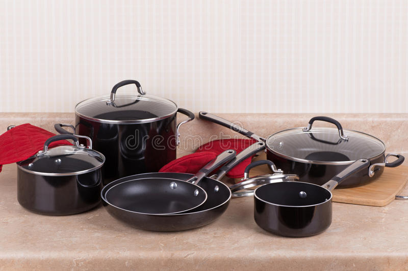 Kitchen Cookware Set. Set of black aluminum cookware on a kitchen counter stock photos