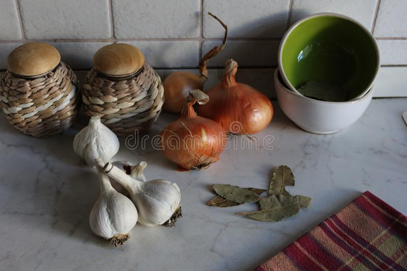 Kitchen corner with white garlic cloves, golden onions, pots and tea towel royalty free stock image