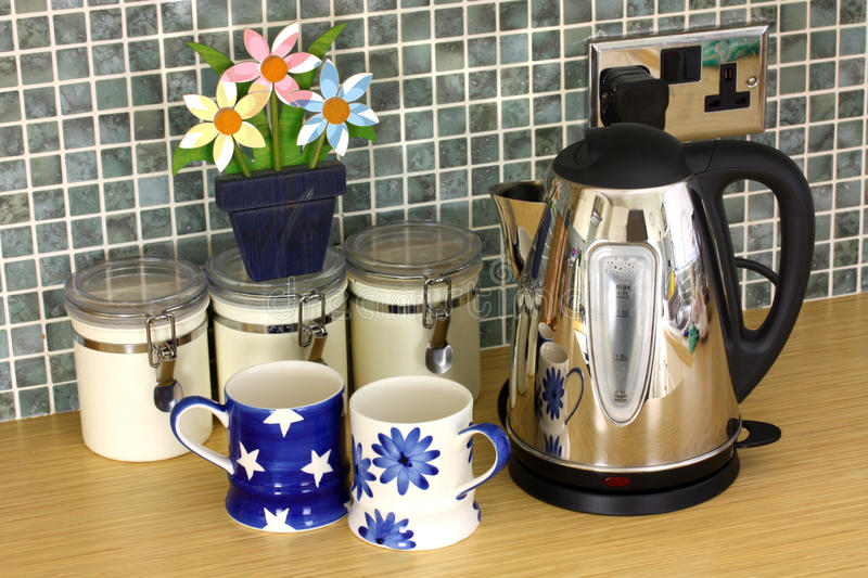 Kitchen counter with kettle and cups and flowers stock images