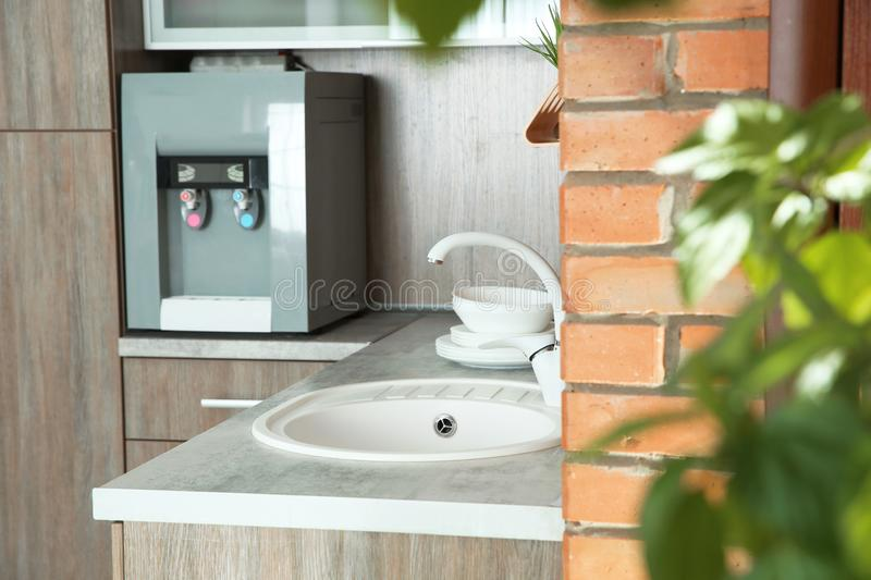 Kitchen counter with water cooler, sink and clean dishes. Indoors stock photo