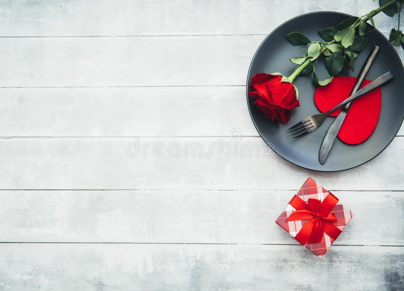 Kitchen cutlery on plate with gift and red rose. Happy Valentines Day. Scene royalty free stock image