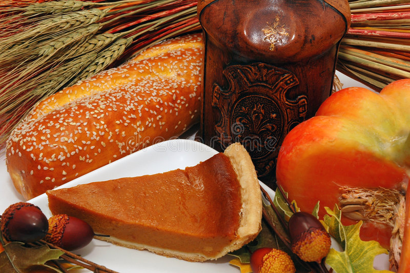 Kitchen Decoration. Pumpkin pie, pumpkin, wheat, bread, acorns, and leather wine bottle royalty free stock images