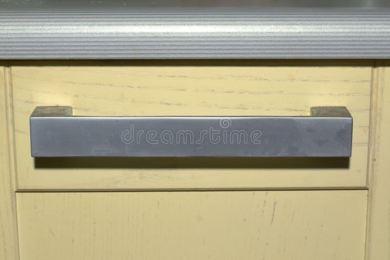 Kitchen drawer knob under the striped worktop. flat arch handle. Kitchen drawer knob under striped worktop. flat arch large handle with sharp corners. Silver stock photo