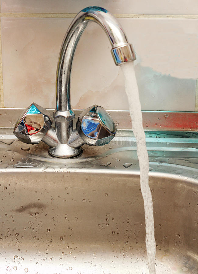 From the kitchen faucet flowing water. royalty free stock photography