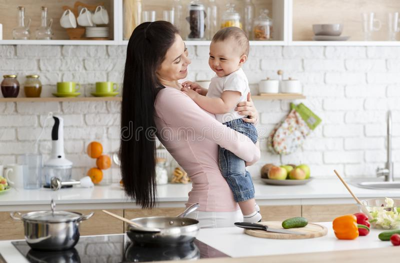 Little baby laughing on mother hands, in kitchen stock photo