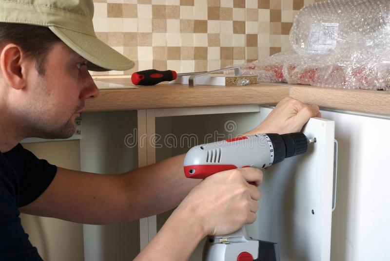 Kitchen furniture installation. Man is fastening the handle to cabinet. stock photos