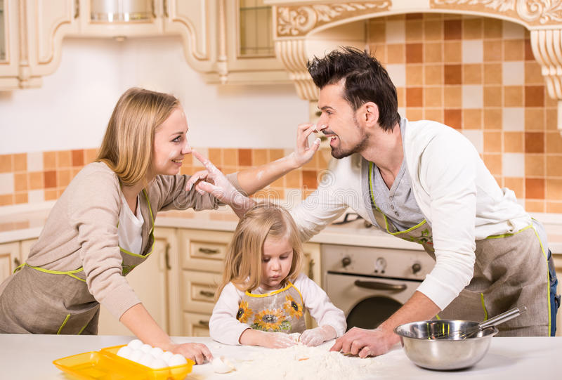 Kitchen. Happy parents and their young daughter are cooking, baking cakes in home kitchen royalty free stock images