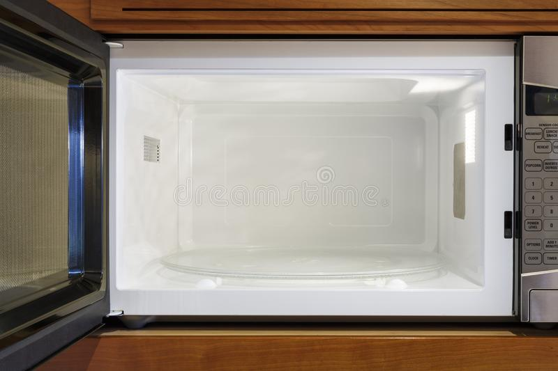 Kitchen home electric appliances interior inside view of open, empty, clean microwave oven stock photo