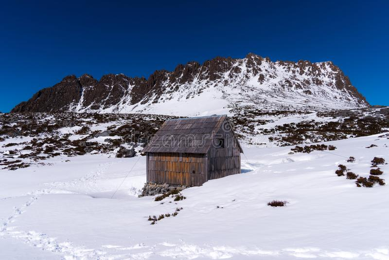 Kitchen hut with a background of the summit of Cradle Mountain in winter. Snowy track to kitchen hut at Cradle Mountain, Tasmania royalty free stock photo