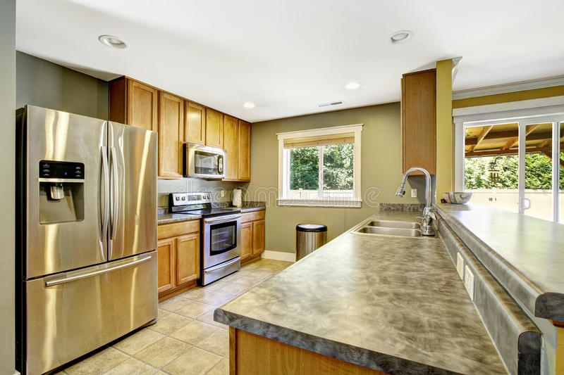 Kitchen interior. Granite tops and steel appliances. Light olive kitchen interior. Steel appliances and wooden cabinets royalty free stock photography