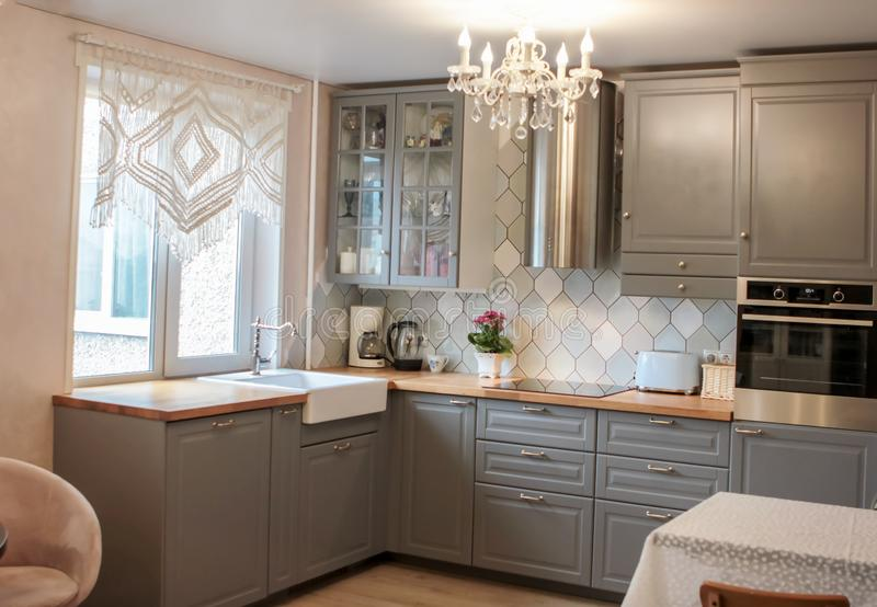 Kitchen interior in grey colors stove refrigerator chairs, class royalty free stock photo
