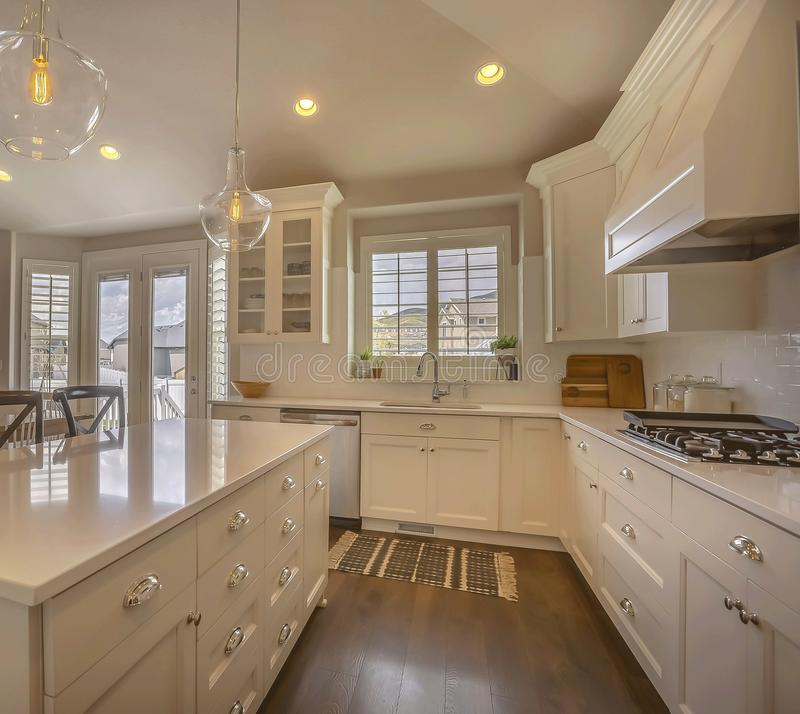 Kitchen interior of a home with island white cabinets cooktop sink and faucet. Round ceiling lights, hanging glass lights, windows and glass doors can also be stock photos