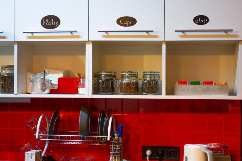 Kitchen interior at home or small office. Red tile wall and white shelf. Cabinet doors with text labels. Glass jars with coffee, stock photos