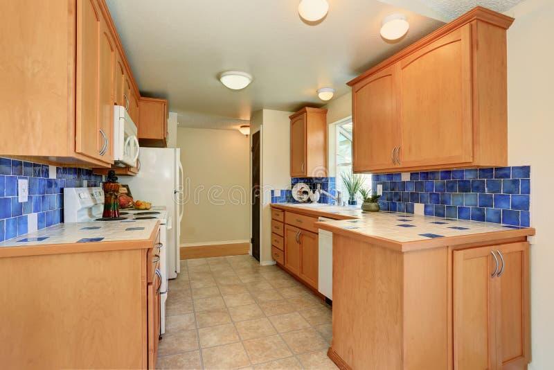 Maple Cabinets With Blue Tile Back Splash Trim And White Appliances.  Northwest, USA