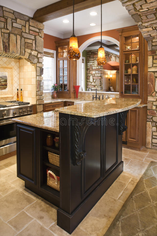 Kitchen Interior With Stone Accents in Affluent Ho. Upscale kitchen interior with stone accents and wood beam ceiling. Vertical shot royalty free stock photo