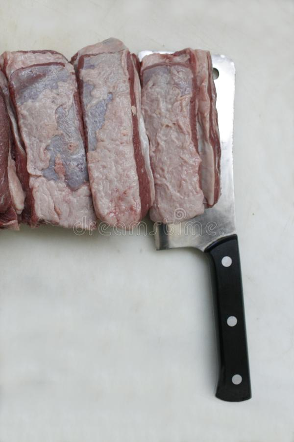 Kitchen knife and beef meat cut into big slices on white cutting board. royalty free stock photo