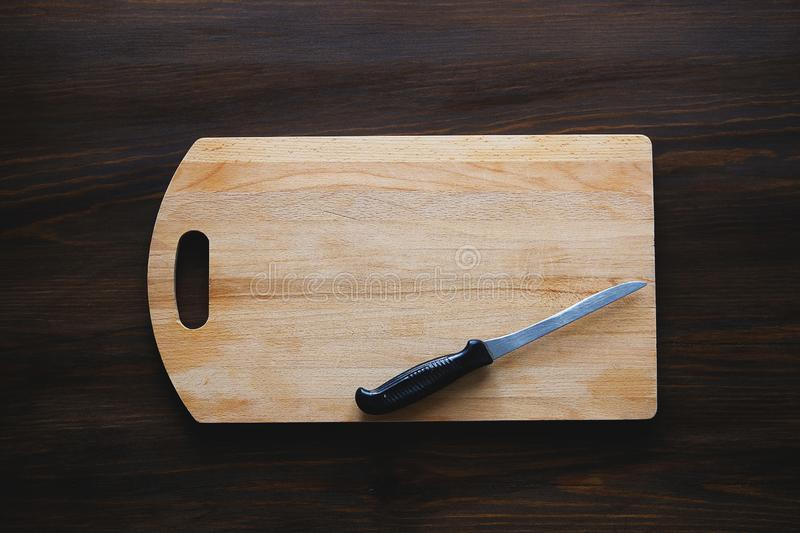 Kitchen knife with black plastic handle on a wooden cutting Board, close-up. Copy space for text. The concept of kitchen utensils stock photo