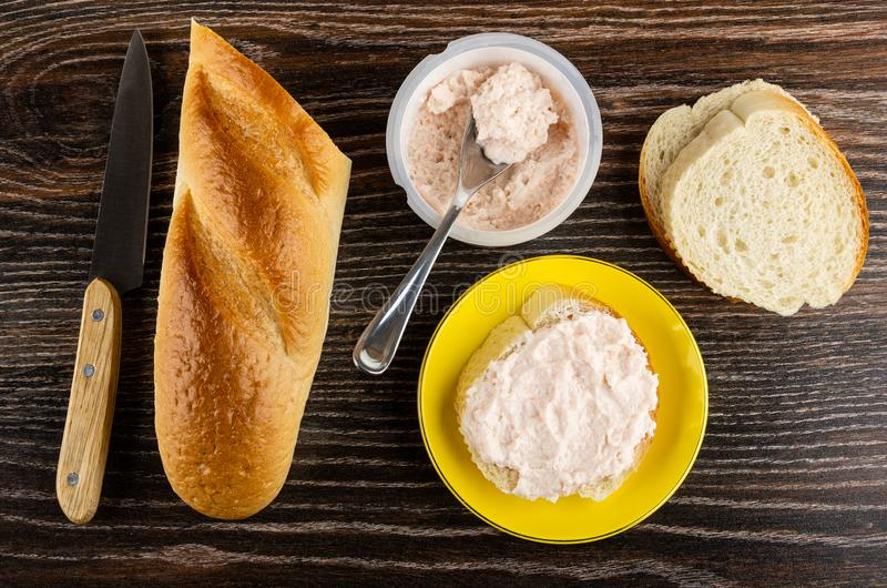 Knife, loaf of bread, sandwich with krill paste in saucer, spoon in jar with paste on wooden table. Top view. Kitchen knife, loaf of bread, sandwich with krill royalty free stock photography