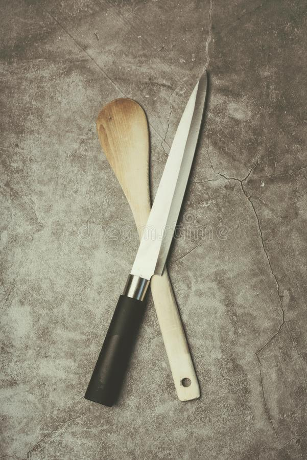 Kitchen knife and Wooden spoon. Against Grunge background royalty free stock photo
