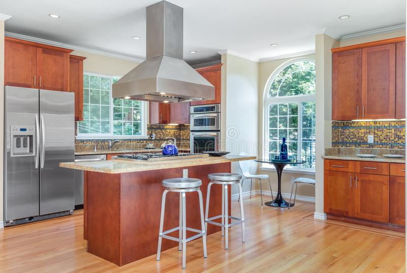 Kitchen in luxury home with stainless steel appliances. Kitchen in luxury home with stainless steel appliances, granite work surfaces, bar stools and wooden royalty free stock images