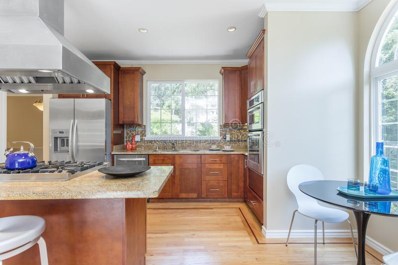 Kitchen in luxury home with stainless steel appliances. Kitchen in luxury home with stainless steel appliances, granite work surfaces, bar stools and wooden stock photo