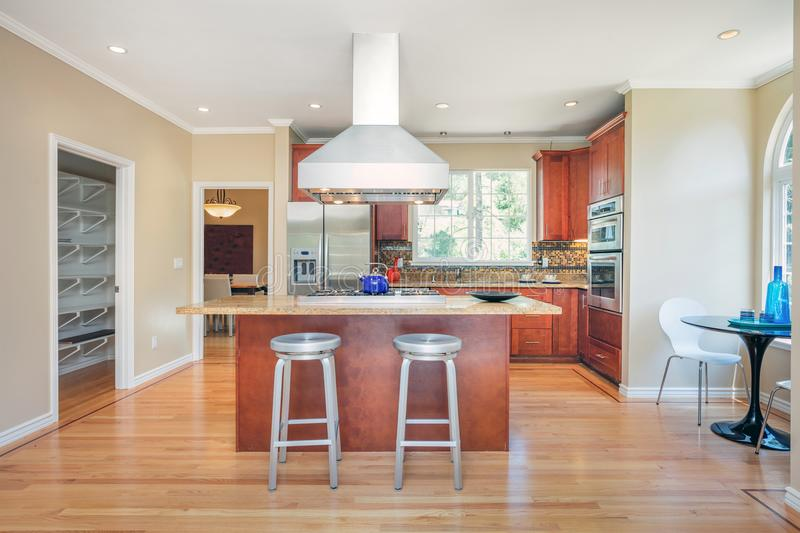 Kitchen in luxury home with stainless steel appliances. Kitchen in luxury home with stainless steel appliances, granite work surfaces, bar stools and wooden royalty free stock photo