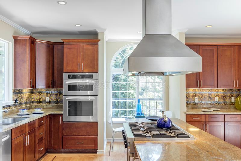 Kitchen in luxury home with stainless steel appliances. Wooden Kitchen in luxury home with stainless steel appliances, granite work surfaces, bar stools and stock image