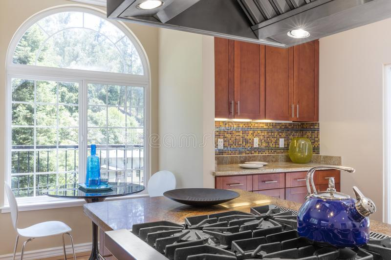 Kitchen in luxury home with stainless steel appliances. Wooden Kitchen in luxury home with stainless steel appliances, granite work surfaces, bar stools and stock photography